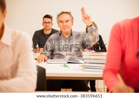 Group of people of different age sitting in classroom and attending a school for adults. Lifelong learning. - stock photo