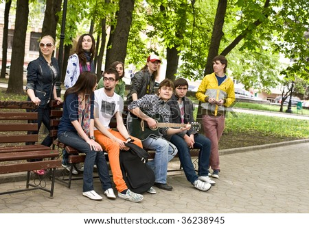 Group of people on bench in park. Outdoor. - stock photo