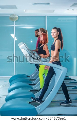 Group of people on fitness sports. Sport and slender girl running on a treadmill and looking at the camera. Athlete dressed in sports uniforms and running in the gym. - stock photo