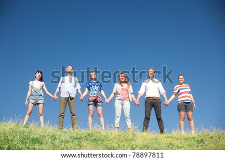 Group of people on hill hold hands together across blue sky - stock photo