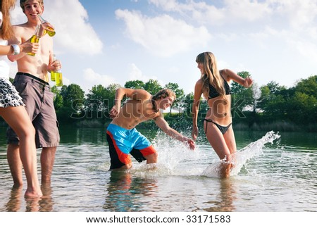 Group of people on the beach of a lake - one couple is chasing each other through the water - stock photo