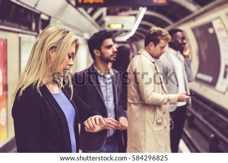 Group of people on the platform at train station in London. They are a mixed group of persons, wearing smart casual clothes. Friends or just strangers. Urban lifestyle and transportation concepts.