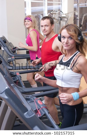 Group of people on trainer machine in sport gym