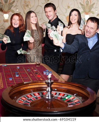 Group of people play roulette in casino - stock photo