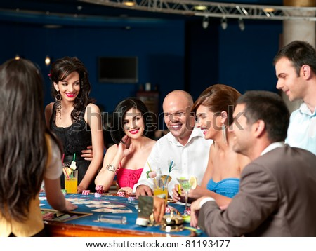 group of people playing blackjack or poker, smiling - stock photo