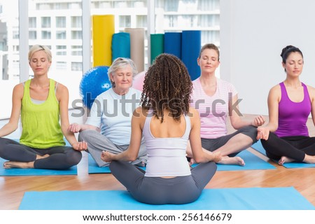 Group of people practicing lotus position in yoga class - stock photo