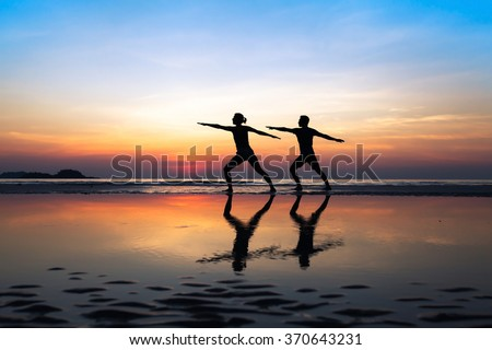 group of people practicing yoga, couple doing stretchings on the beach at sunset