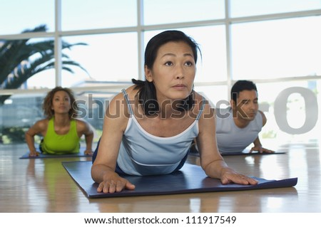 Group of people practicing yoga on the floor - stock photo