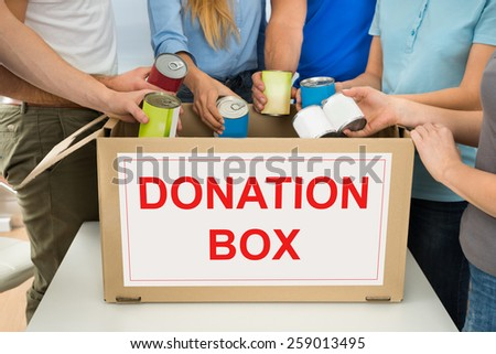 Group Of People Putting Cans In Donation Box - stock photo