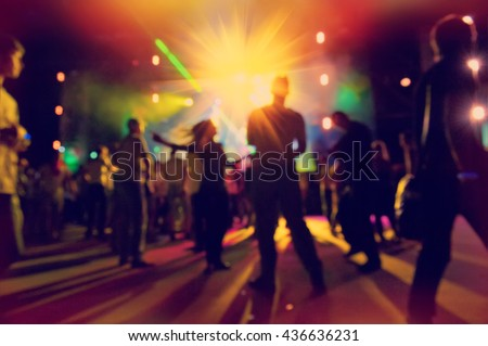 group of people relaxing and having fun at the disco, blurred background