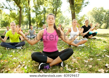 group of people relaxing with meditation in park - stock photo