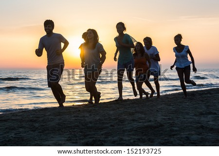 Group of People Running on the Beach at Sunset - stock photo