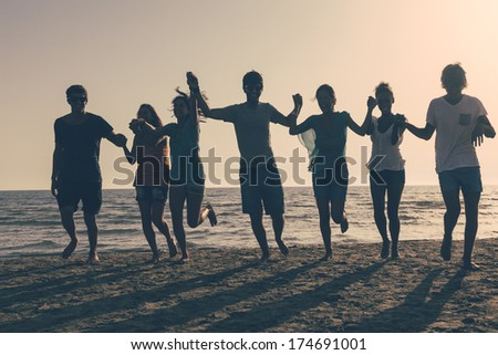 Group of People Running on the Beach at Sunset