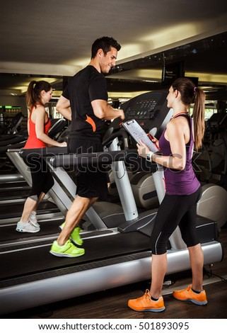 Group of people running on treadmills with a coach