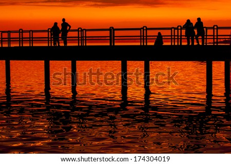 Group of people silhouette on boardwalk at sunset - stock photo