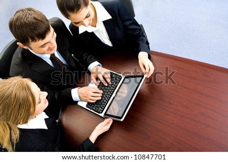 Group of people sitting at the table and working on the laptop - stock photo