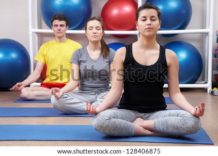 Group  of people sitting in pose lotus yoga on mates in gym - stock photo