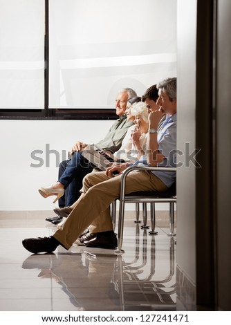 Group of people sitting in waiting area of hospital - stock photo