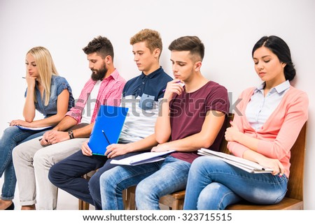 Group of people sitting on chairs waiting interviews - stock photo