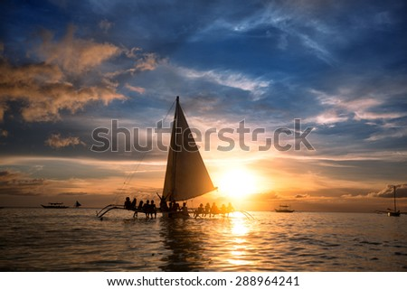 Group of people sitting on sailboat at  ocean and looking  sunset