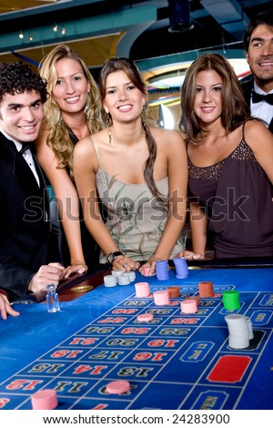 Group of people smiling playing roulette at a casino - stock photo