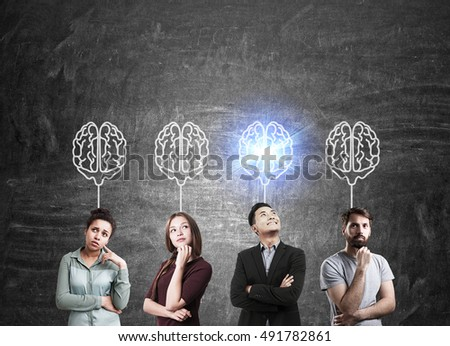 Group of people standing near chalkboard with brain sketches. One of them is shining. Concept of teamwork