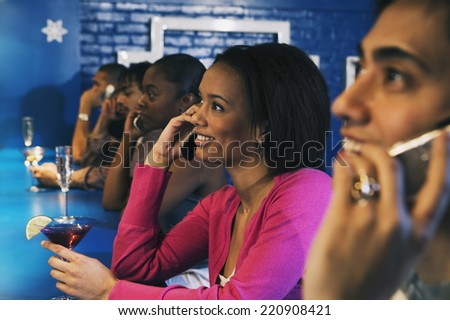 Group of people talking on cell phones at bar - stock photo