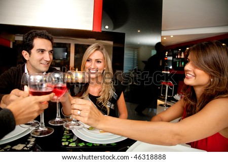 Group of people toasting looking happy at a fancy restaurant - stock photo
