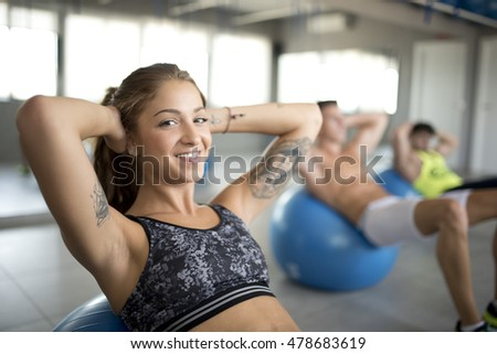 Group of people training abdominal muscle in gym room