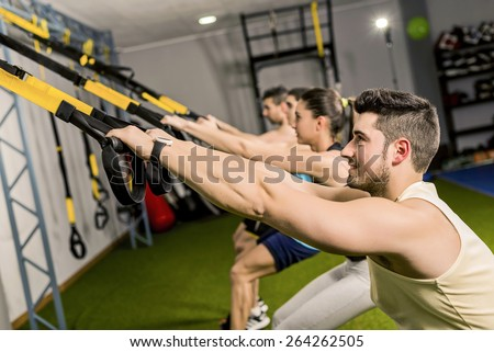 Group of people training in elastic rope at modern gym