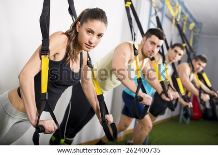 Group of people training in suspension elastic rope at gym and looking at the view - stock photo