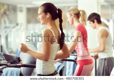 Group of people training on treadmill in gym