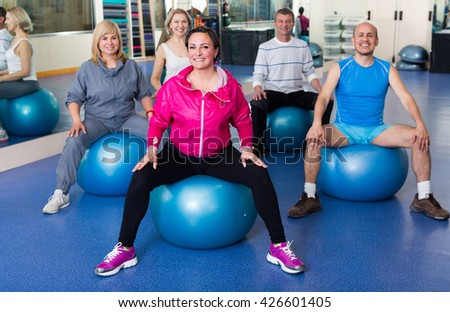 Group of people training with balls in  fitness club. Selective focus  - stock photo