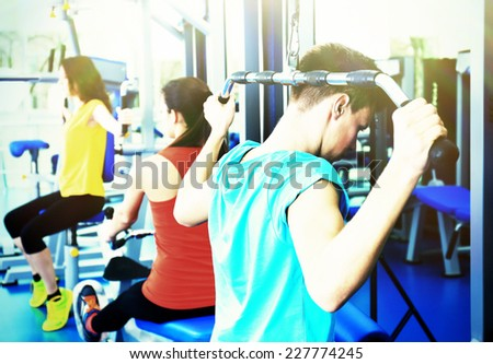 Group of people training with weights in gym - stock photo