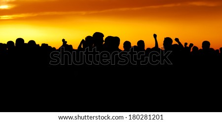 Group of people walking at sunset