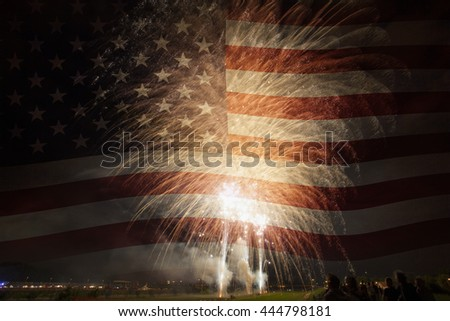 Group of people watching colorful fireworks in the sky with American flag in background. 4th of July concept.
