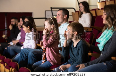 Group of people watching funny movie in cinema house