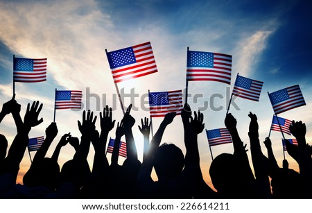 Group of People Waving American Flags at Sunset - stock photo