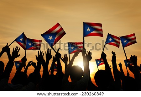 Group of People Waving Flag of Puerto Rico in Back Lit - stock photo