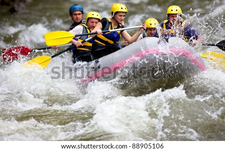 Group of people whitewater rafting and rowing on river