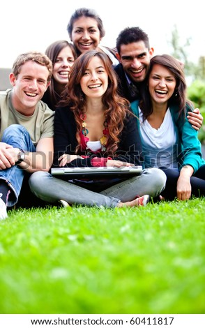 Group of people with a laptop outdoors and smiling - stock photo