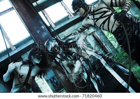 group of people with agressive face-art. zombie style. shot in destroyed building - stock photo