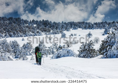group of people with backpacks walking along the trail in winter mountains - stock photo