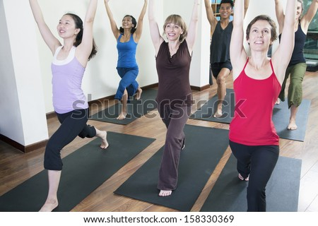 Group of people with hands raised doing yoga during a yoga class - stock photo