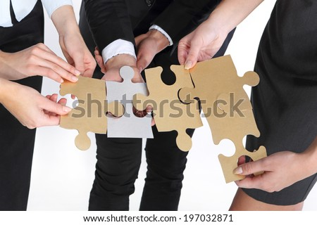 Group of people with huge silver and gold jigsaw puzzle pieces.