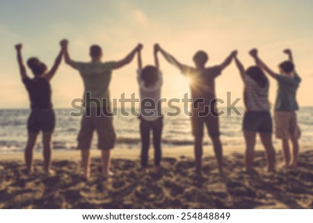 Group of people with raised arms at seaside, blurred background. Backlight shot. Happiness, success, friendship and community concepts. - stock photo