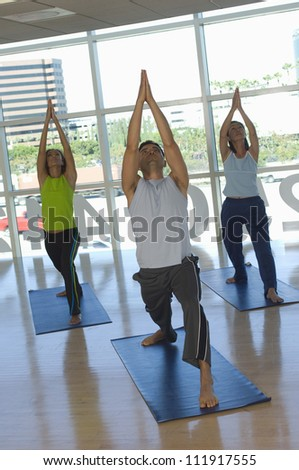 Group of people with raised arms when practicing yoga - stock photo