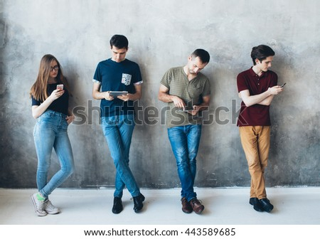 Group of people with telephone tablet using near gray wall  - stock photo