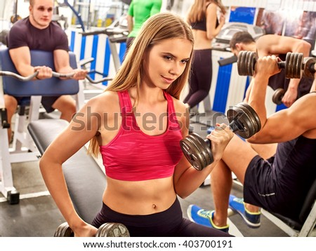 Group of people working with  dumbbells his body at gym.  The girl in a red tank top in the foreground. - stock photo