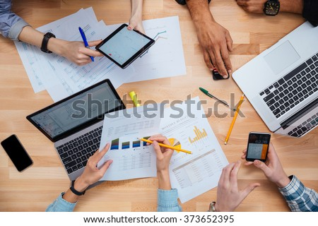 Group of people working with laptops, tablet and smartphones together and making financial report